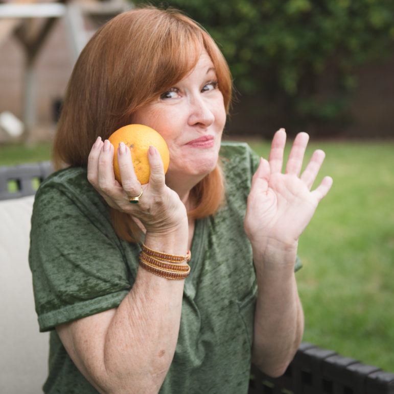 A fruit donor holds up a piece of fruit from her tree