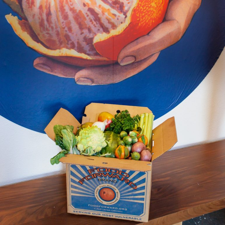 A box of fruits and vegetables in front of orange art