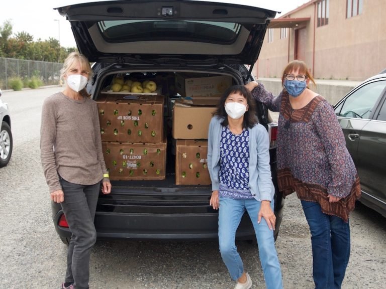 Three woman wearing face masks stand in front of a car trunk filled with produce boxes