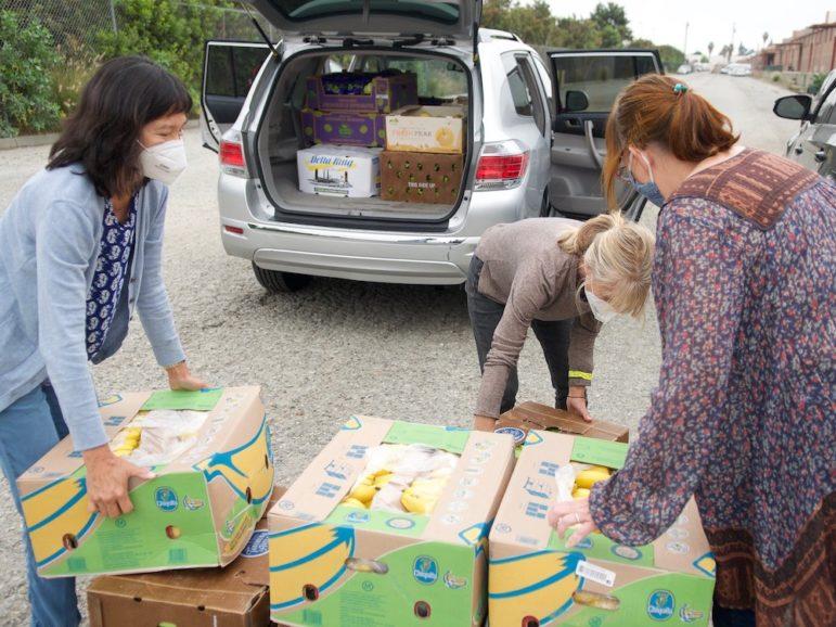 Three women wearing face masks move boxes of bananas