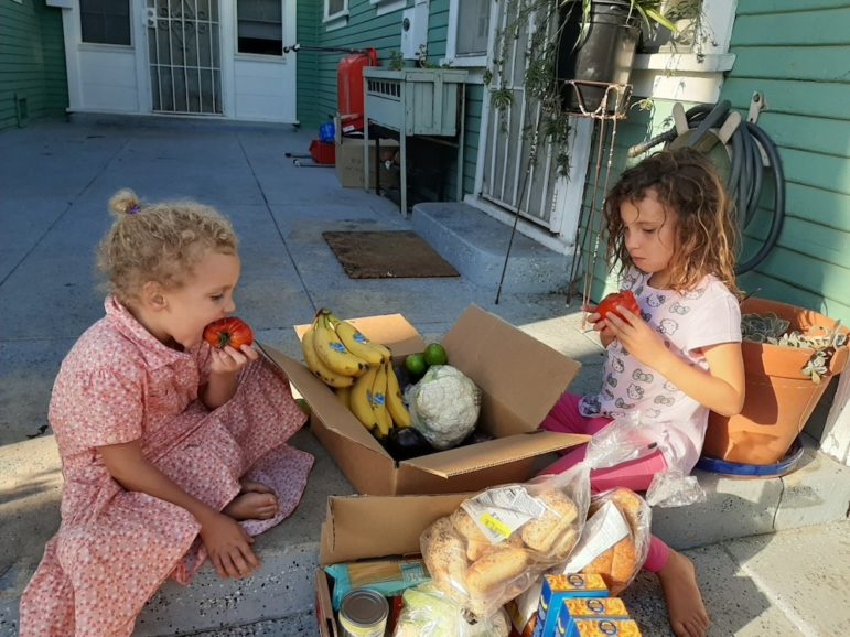 Two young girls sit around a box of food and bite into red tomatoes