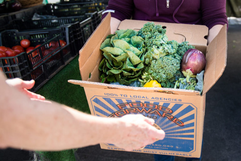 A farmers market vendor hands a Food Forward volunteer a box filled with various vegetables.
