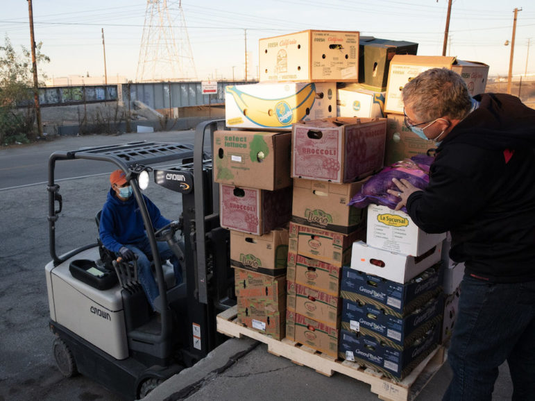Food Forward staff load a pallet stacked with boxes of produce onto a forklift.