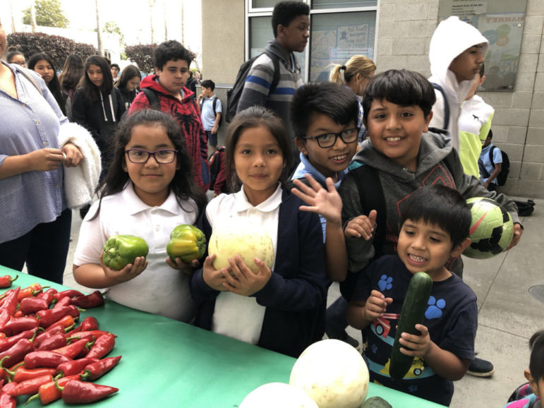 Five young children wave and hold up different fruits and vegetables at a Food Forward produce distribution.