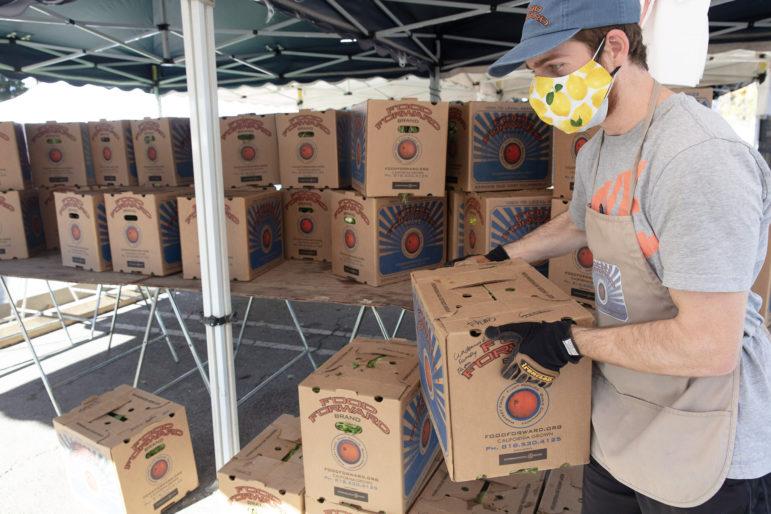 A volunteer at a farmers market moves Food Forward boxes